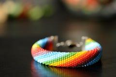 Gewirktes Armband der Perle von Farben eines Regenbogens Stockfotografie