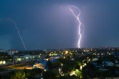 Gewitter über Stadt im Blaulicht Stockfotografie