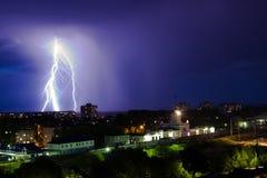 Gewitter über Stadt im purpurroten Licht Stockfotos