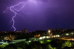 Gewitter über Stadt im purpurroten Licht Stockbild
