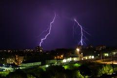 Gewitter über Stadt im purpurroten Licht Stockbilder