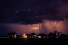 Gewitter mit zwei Blitzen, die Gebäude um die Stadt schlagen Stockfoto