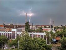 Gewitter und dunkle Wolken über der Stadt und dem Industriegebiet Lizenzfreie Stockfotos
