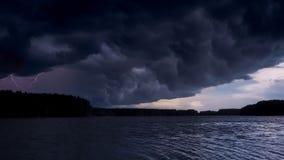 Gewitterwolke überschattet die Sonne Stürmischer Himmel über dem Abendflusssee Stockfotografie
