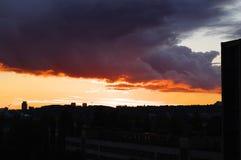 Gewitterwolken auf dem roten Sonnenuntergang in der Stadt stockfotografie