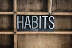 Gewohnheits-Konzept-Metallbriefbeschwerer-Wort im Fach Stockfotos