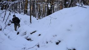 Gewonde militair die door de sneeuw in het bos lopen stock footage