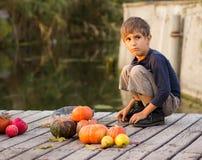 Gewone jongenszitting met Halloween-pompoenen Royalty-vrije Stock Fotografie
