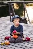 Gewone jongenszitting met pompoenen en appelen Stock Afbeelding