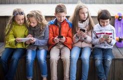 Gewone kinderen die met de telefoon op bank in openlucht spelen stock fotografie