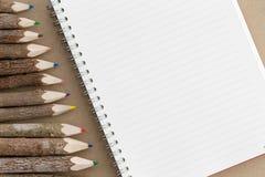 Gewundenes es-gehend Notizbuch mit farbigen Bleistiftzeichenstiften Stockbild