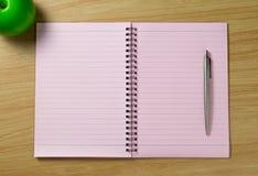 Gewundenes Notizbuch auf dem Schreibtischhintergrund Stockfotografie