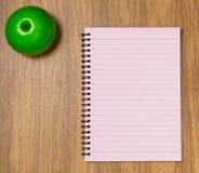 Gewundenes Notizbuch auf dem Schreibtischhintergrund Lizenzfreies Stockbild
