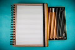 Gewundenes Notizbuch und Bleistifte Stockbild