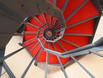 Gewundenes Treppenhaus mit rotem Teppich Stockfotografie