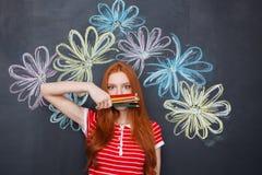 Gewunderte Frau bedeckte Gesicht mit den bunten Bleistiften, die über Tafel stehen Stockbild