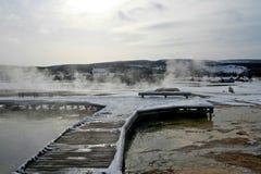 Geyserånga som stiger av trästrandpromenad i vinter på gammalt troget område i den Yellowstone nationalparken i USA fotografering för bildbyråer