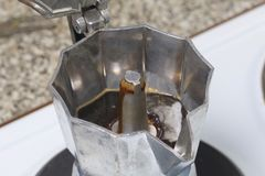 A geyser coffee machine is on the electric stove. It is visible as ready coffee under pressure pours out in the container. A geyser coffee machine is on the Stock Photo
