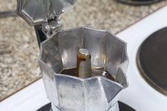 A geyser coffee machine is on the electric stove. It is visible as ready coffee under pressure pours out in the container. A geyser coffee machine is on the Stock Images