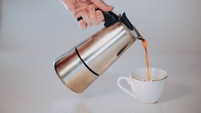 Geyser coffee makers coffee poured in a white Cup, white background. slpw motion stock footage