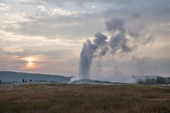 Geyser erupting against a colorful sunset stock photography
