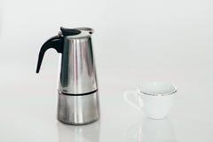 Geyserkaffebryggare och en kopp för vitt kaffe som isoleras på vit arkivfoto
