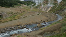 Geysernaya River in Valley of Geysers stock footage video. Geysernaya River in Valley of Geysers. Kamchatka Peninsula in the summer stock footage video stock footage