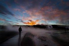 Geysers de Yellowstone do nascer do sol com o homem mostrado em silhueta Fotografia de Stock Royalty Free