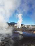 Geysers at El Tatio in Chile. Plumes of steam rising from the ground in the early morning near San Pedro de Atacama. Geysers letting of water vapour, Reflections Royalty Free Stock Photo