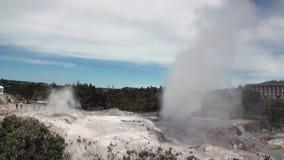 Geysers Hot Springs no fundo do horizonte da floresta e do céu em Nova Zelândia filme