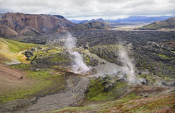 Geysers  throwing out steam against a volcano cone Royalty Free Stock Images