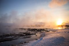 Geysir eruption inIceland against sunset. Touristic attraction, people watching epic geysir eruption in Iceland in the evening, hot springs Royalty Free Stock Photography