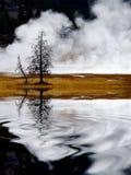 Geysire und Dampf, die in die Yellowstone Nationalpark Reflexion sich reflektiert im Wasser-Teich oder dem See steigt lizenzfreies stockbild