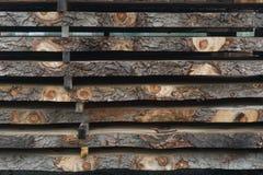 Gezaagde die logboeken in een stapel bij de zaagmolen worden gestapeld stock afbeeldingen