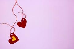 Gezeiten mit zwei Papierherzen zu einer Schnur auf einem rosa Hintergrund Lizenzfreies Stockbild