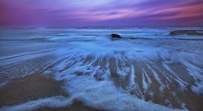 Gezeiten und Moonrise über sandigem Ozean vertiefend, setzen Sie auf den Strand Stockfoto