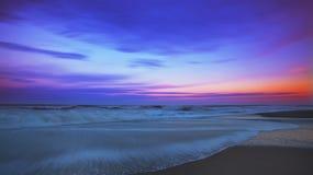 Gezeiten und Moonrise über sandigem Ozean vertiefend, setzen Sie auf den Strand Stockbild