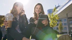 Gezellige Kaukasische meisjes die de tabletcomputer met behulp van die bij pretbeelden lachen op de tabletzitting in openlucht in stock videobeelden