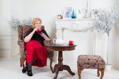 Gezet in een stoel volwassen vrouw het drinken thee Stock Afbeeldingen