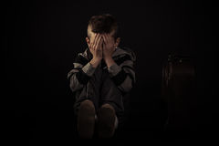 Gezette Doen schrikken Jongen die zijn Gezicht behandelen tegen Zwarte Stock Foto's