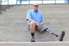 Gezette mens met prothetisch uitgestrekt been Stock Foto