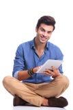 Gezette toevallige mens die aan zijn computer van het tabletstootkussen werken Royalty-vrije Stock Foto