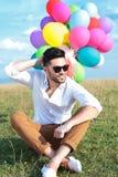 Gezette toevallige mens met het hoofd van ballonskrassen Stock Fotografie