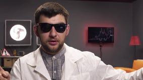 Gezicht die van de gebaarde mens zonnebril en witte laboratoriumlaag het dragen spreekt vreugdevol stock video