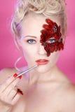 Gezicht met rode veren en een lippenborstel Royalty-vrije Stock Afbeelding