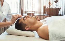 Gezicht van de Cosmetologist het schoonmakende mens met twee sponsen royalty-vrije stock afbeelding