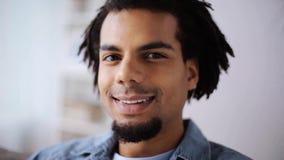 Gezicht van de gelukkige glimlachende afro Amerikaanse mens thuis stock video