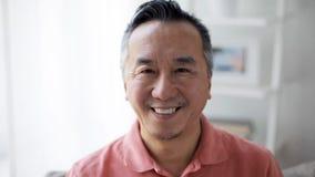 Gezicht van de gelukkige glimlachende Aziatische mens thuis stock footage