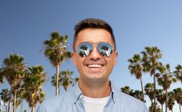 Gezicht van de glimlachende mens in zonnebril over palmen stock foto's