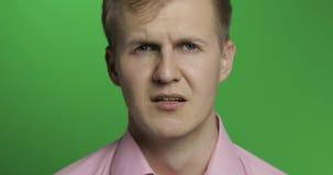 Gezicht van de jonge gedeprimeerde mens die op groene chroma zeer belangrijke achtergrond schreeuwen stock footage